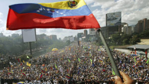 CARACAS, VENEZUELA - NOVEMBER 25: A Venezuelan flag is waved at a rally for opposition presidential candidate Manuel Rosales November 25, 2006 in Caracas, Venezuela. Rosales is challenging President Hugo Chavez in Venezuela's presidential election December 3. (Photo by Mario Tama/Getty Images)